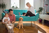 Father sitting on the floor and with baby in his arms playing with dog while wife sitting on sofa and doing online shopping with credit card