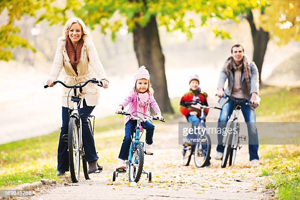 Happy family riding bicycles in nature.