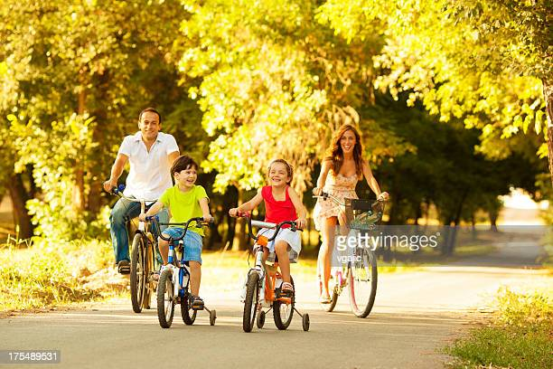 Happy Family Riding Bicycles Outdoors