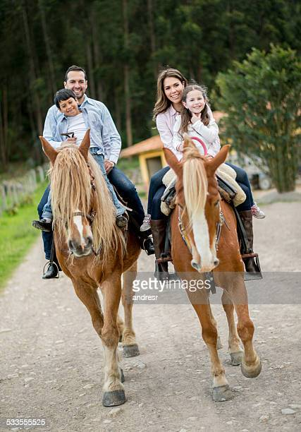 Happy family riding horses