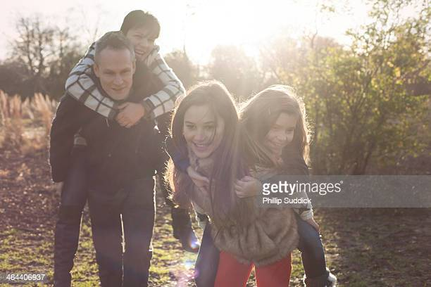 Happy family running in nature on piggyback