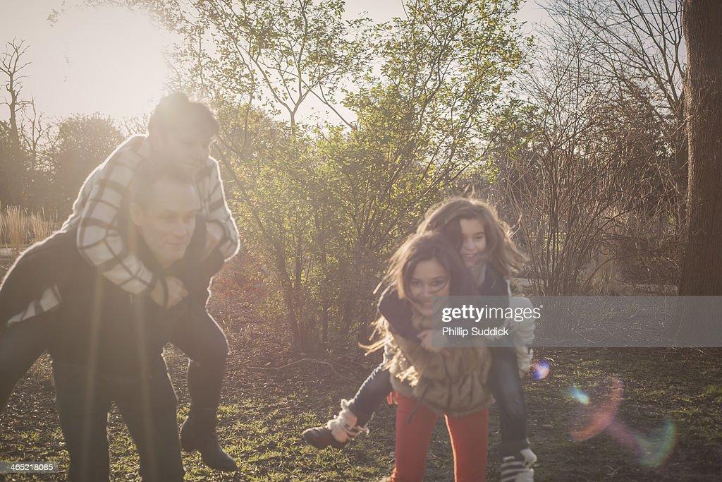Happy family running in nature on piggyback