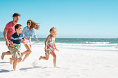 Cheerful young family running on the beach with copy space. Happy mother and smiling father with two children, son and daughter, having fun during summer holiday. Playful casual family enjoying playin