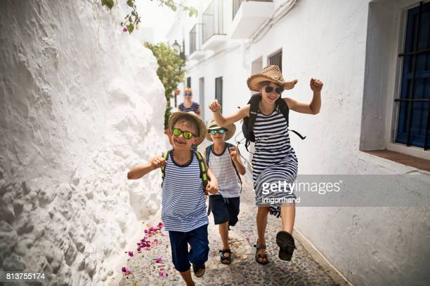 Happy family running on street in andalusian white village