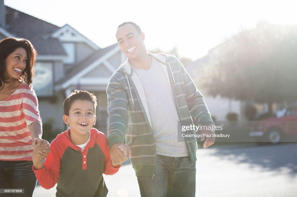 Happy family running on sunny street : Stock Photo