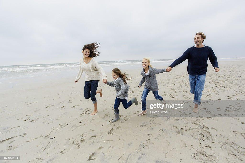 Happy family running on the beach : Stock Photo