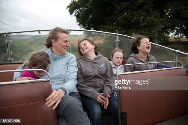 Happy family singing with a mother and her two daughters and nieces on an open top bus in Devon England United Kingdom One grown up and four girls...