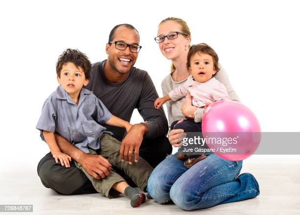 Happy Family Sitting Against White Background