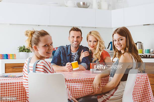 Happy family sitting at the kitchen table