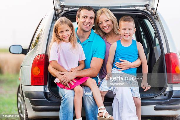 Happy family sitting in a car trunk outdoors.