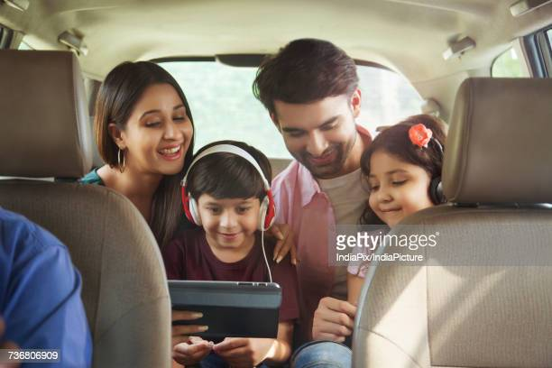 Happy family sitting in back seat of car using digital tablet