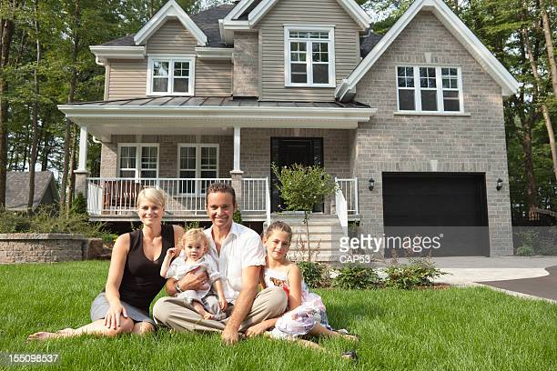 Happy Family Sitting In Front Of Their New House