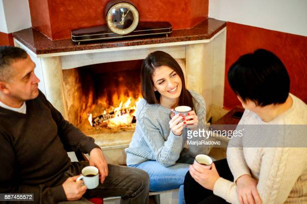 Happy family sitting near fireplace at home drinking coffee, parents and daughte