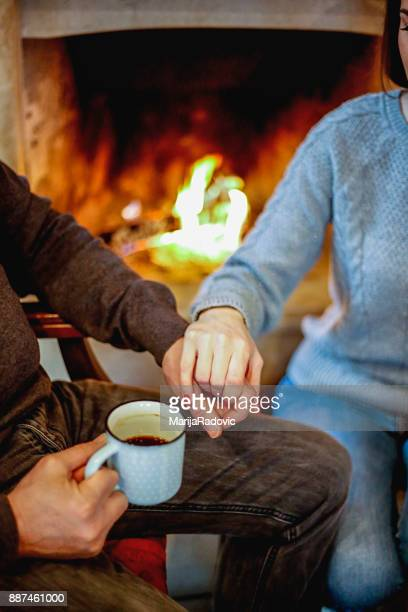 Happy family sitting near fireplace at home drinking coffee, parents and daughter