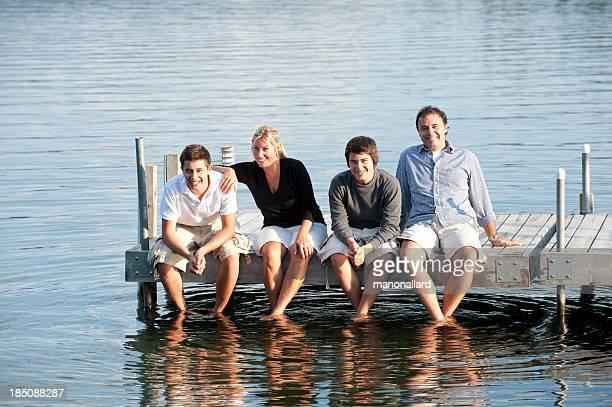 Glückliche Familie sitzt auf einem hölzernen pier's lake