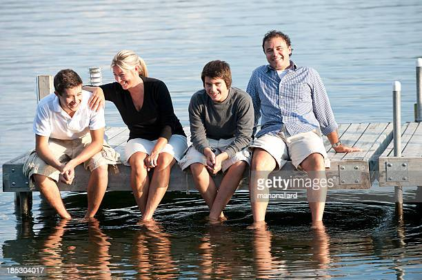 Happy family sitting on a wooden pier's lake
