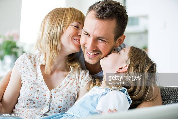 Happy family sitting on couch, mother and daughter kissing father