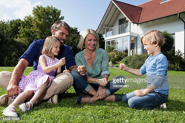Happy family sitting on lawn in garden playing rock-paper-scissors