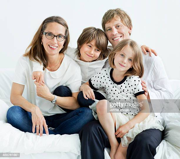Happy family sitting on sofa, studio shot