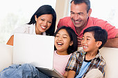 Family in living room with laptop smiling and laughing together