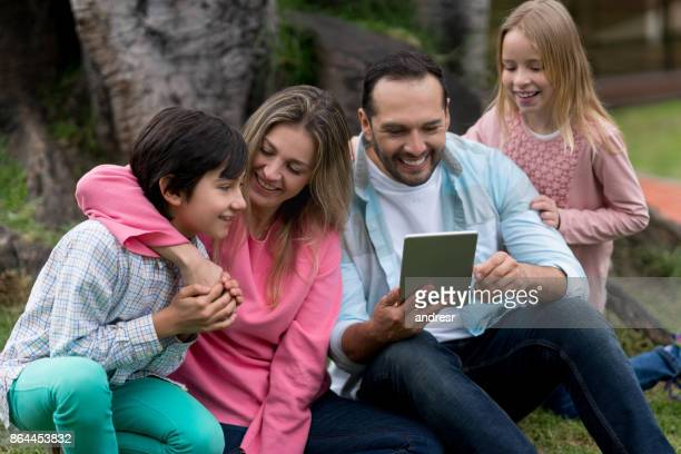 Happy family social networking outdoors on a digital tablet