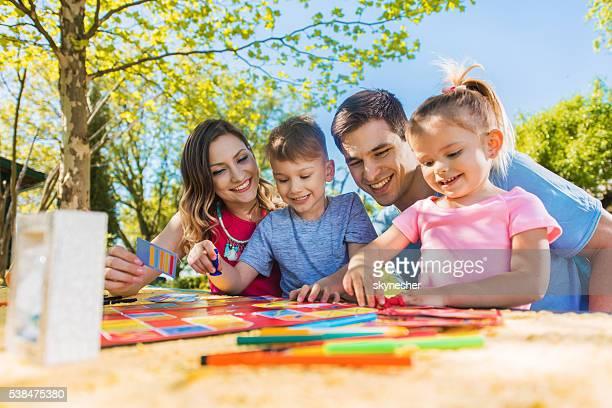 Glückliche Familie, die ein Tag im Freien und spielen Brettspiel.