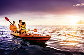 Happy family swimming by kayak at sunset sea