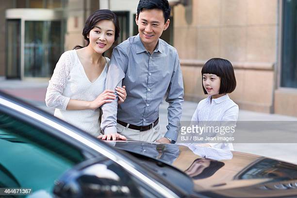 Happy family taking a close look at a new car