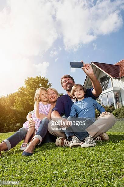 Happy family taking selfie in garden