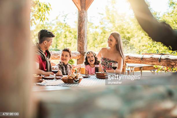 Happy family talking and laughing in a restaurant.