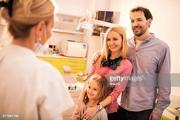 Happy family talking to female dentist at dentist office.