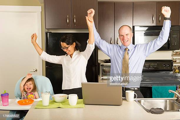 Happy family throwing hands in the air in a kitchen