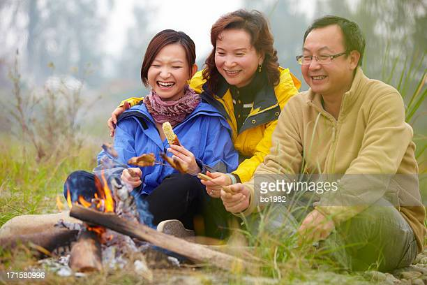 happy family toasting food on campfire outdoors
