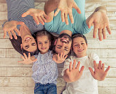 Top view of beautiful young parents, their cute little daughter and son showing palms, looking at camera and smiling, lying on wooden floor