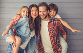Beautiful young parents and their children are looking at camera and smiling, on gray wall background