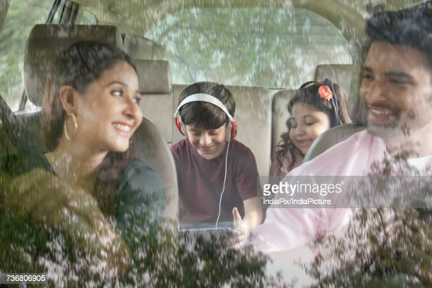 Happy family travelling in car and kid listening music sitting in back seat of car