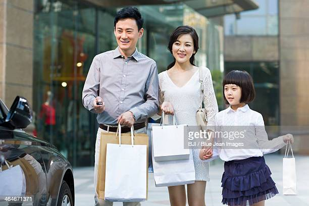 Happy family unlocking car after shopping