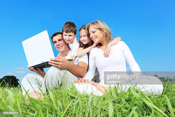Happy family using laptop, sitting on the green grass.