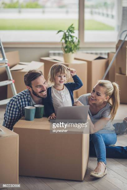 Happy family using laptop while taking a break from unpacking their belongings.