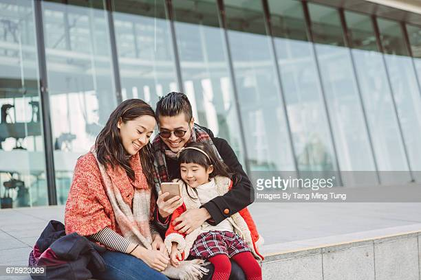 Happy family using smartphone outdoor in winter
