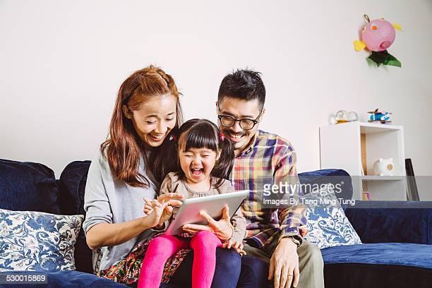 Happy family using tablet joyfully at home