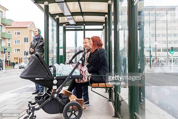 Happy family waiting at bus stop