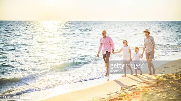 Feliz família caminhar ao longo de uma praia de areia
