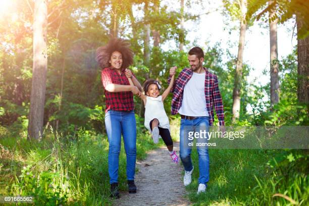 Happy family walking and swinging their daughter.