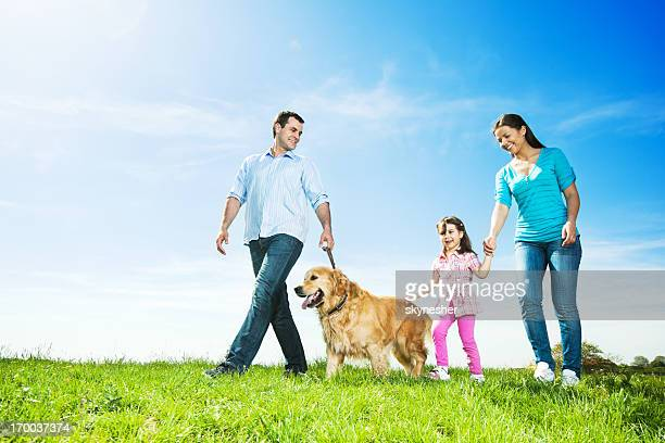 Happy family walking  dog in a park.