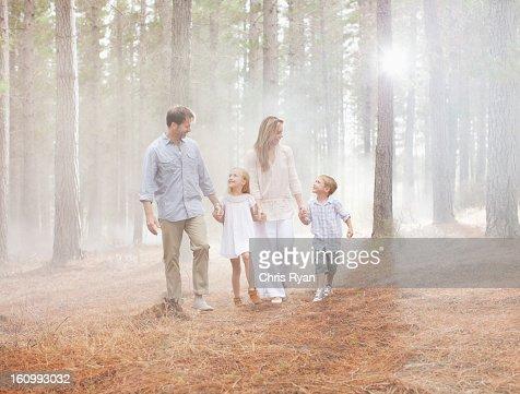 Happy family walking in sunny woods