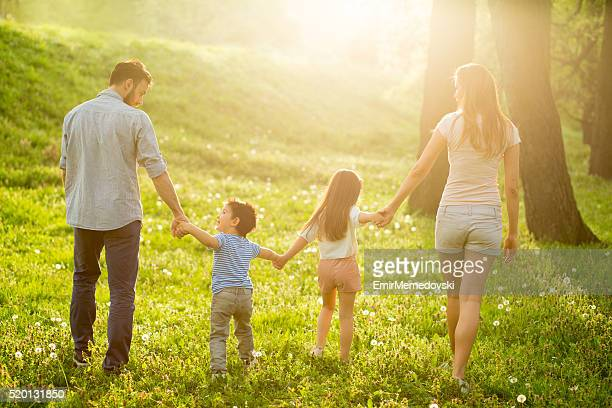 Happy family walking in the park on summer day