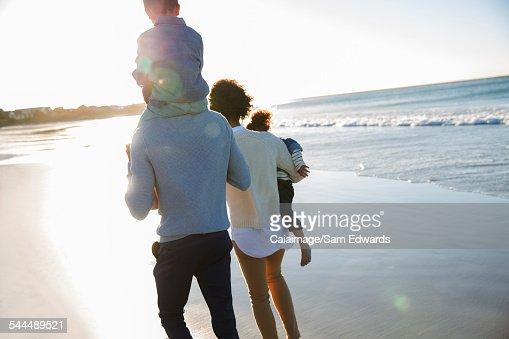 Happy family walking on beach