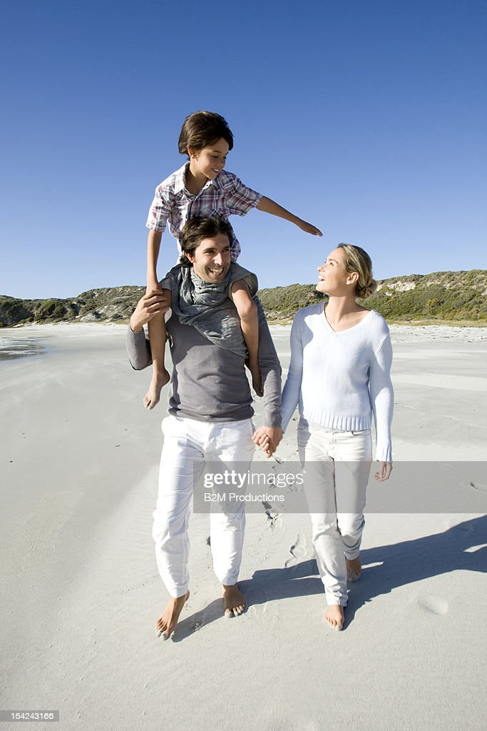 A happy family walking on the beach : Stock Photo