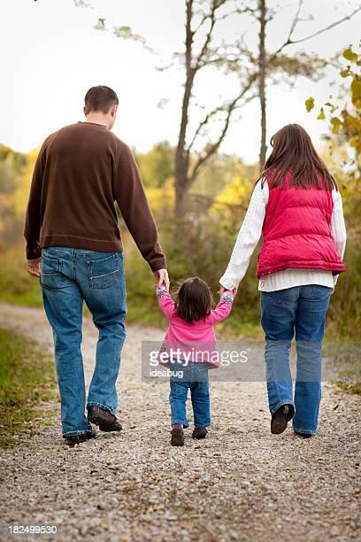 Happy Family Walking on Trail Through Autumn Woods